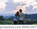 Happy young couple traveler relaxing and looking at the beautiful sunset on the top of mountain 80061007