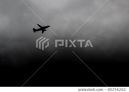 Plane flies away from storm. Silhouette aircraft escape from thunderclouds. Air crash hazard concept. Passenger airliner on a background of a hurricane 80256202