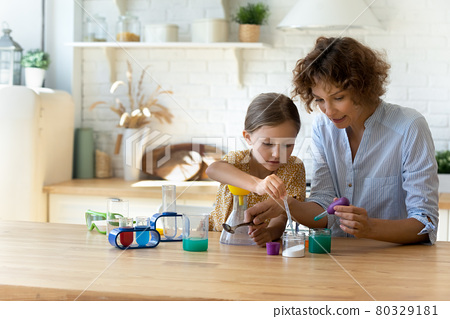Concentrated small kid doing experiments with mum at home. 80329181