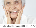 Happy senior woman is smiling confidently at beauty of new denture,false teeth in her mouth,beautiful old elderly showing new teeth after treatment,orthodontics,oral hygiene,dental health,care concept 80330277