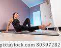 Sporty slim caucasian woman doing self massage on fitness mat with massage ball indoors. Self-isolation massage 80397282
