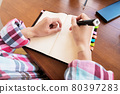 Young Caucasian attractive woman taking notes in her notebook while sitting in the kitchen at the table. Paper notebook writing female hands 80397283