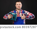 Portrait of a friendly carpenter with an electric jigsaw in his hand showing a thumb up. Studio shot on black background 80397287