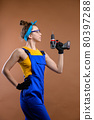 Young woman repairman in overalls and goggles works with a screwdriver in the studio on a brown background. Focus on the screwdriver. Copy space 80397288