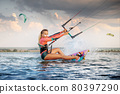 Front view Professional kite surfer woman rides on a board with a plank in her hands on a leman lake with sea water at evening. Water splashes and sun glare. Water sports 80397290