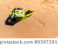 Snorkeling equipment on the sand with ocean waves splashing the water. Black fins, black mask, snorkel on sandy texture background. Items lying in the sand 80397291