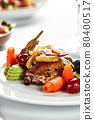 Grilled quail with vegetable stew, light plate table with white tablecloth and cutlery 80400517