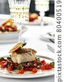 Black cod fillet on a vegetable stew, festive serving on a white grater on a table with white tablecloths. 80400519