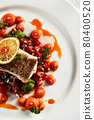 Black cod fillet on a vegetable stew, festive serving on a white grater on a table with white tablecloths. 80400520
