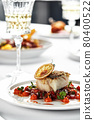 Black cod fillet on a vegetable stew, festive serving on a white grater on a table with white tablecloths. 80400522