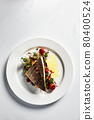 Grilled seabass with vegetables top view, close-up, white plate, light background, copy space 80400524