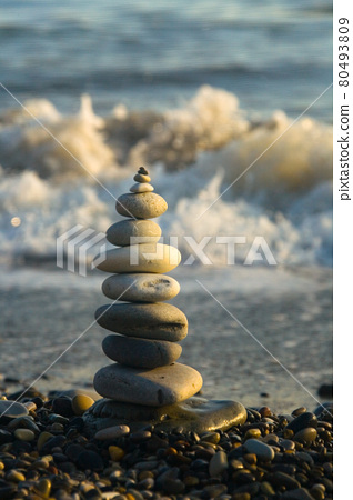 A beautiful pyramid made of stones on the seashore. 80493809
