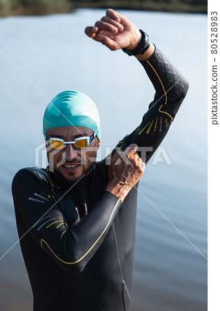 Professional triathlete before swimming in river's open water. Man wearing swim equipment practicing triathlon on the beach in summer's day. 80528983