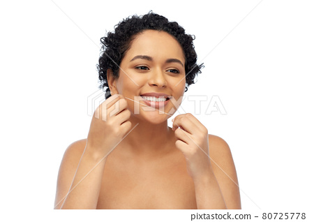 african woman cleaning teeth with dental floss 80725778