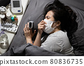 Ill woman patient with fever cough lying in bed at her home,Coronavirus crisis,hospital bed is full during COVID-19 pandemic,self-treatment while waiting for hospital bed,home isolation quarantine 80836735