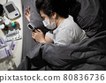 Infected asian woman lies in bed,taking care of herself with medication from doctor,fever from Coronavirus infection during COVID-19 pandemic,quarantine,self-isolation,medical treatment at her home 80836736