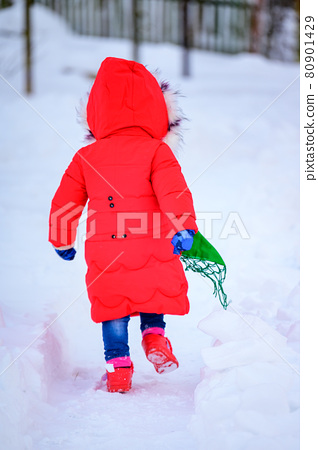 A happy girl in a red jacket and Ukrainian national kerchief walks in a snowy yard. 80901429