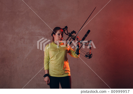 Archer woman with modern block sport bow and arrow indoor 80999957