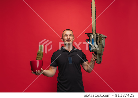 One young caucasian man with cactus and electric saw posing over red background. 81187425