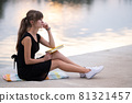 Female student sitting in summer park reading textbook outdoors. Education and sudy concept. 81321457
