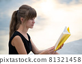 Female student sitting in summer park reading textbook outdoors. Education and sudy concept. 81321458
