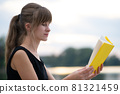 Young woman resting in summer park reading a book. Education and sudy concept. 81321459