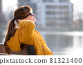 Young woman sitting on park bench relaxing on warm spring day. 81321460