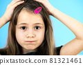 Close up portrait of upset and pensive little girl with cute pink hairpin on blue background. 81321461