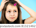 Close up portrait of upset and pensive little girl with cute pink hairpin on blue background. 81321462