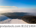 Aerial view of winter landscape with foggy countryside and distant factory pipes emmiting black dirty smoke polluting environment. 81321464