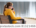 Young pretty woman sitting on a park bench talking on her smartphone outdoors in warm autumn evening. 81321466