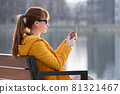 Young pretty woman sitting on a park bench browsing her smartphone outdoors on warm autumn day. 81321467