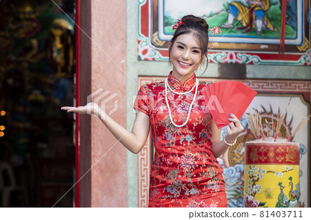 Concept to celebrate Chinese New Year : Chinese woman in a red cheongsam (qipao) dress holding red envelopes (hong bao) at shrine. 81403711