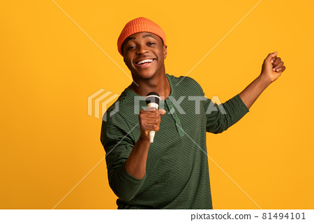 Cheerful Black Millennial Guy Holding Microphone And Singing At Camera 81494101