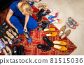 Top view stylish blonde female posing choosing shoes sitting on floor at boutique enjoying shopping 81515036