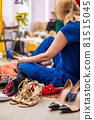 Happy blonde female trying shoes at fashion studio or boutique spending time during shopping 81515045