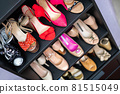 Gray closet shelves full of fashion female shoes on heels pair storage organization of cupboard 81515049