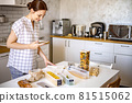 Smiling young beautiful business female taking writes a list of products to buy in paper diary at modern Nordic style kitchen 81515062