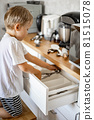 The boy helps his mother in the kitchen to put things in order. Places forks, spoons and cutlery in place. 81515078