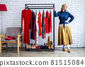 Fashion woman posing with clothes rack full of trendy clothing, shoes and accessories at loft studio 81515084