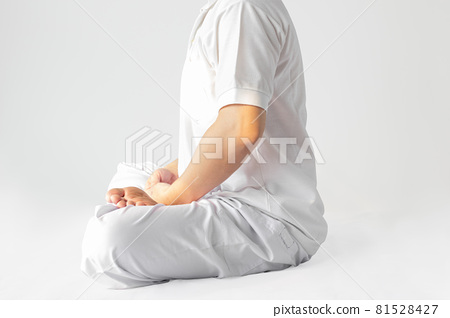 A man in a white robe meditating against a white backdrop with a clipping path. 81528427