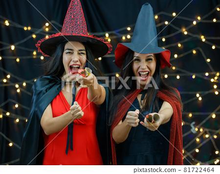 Joyful women in Halloween costumes with serpentine crackers 81722464