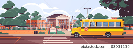 school building empty front yard with green trees road crosswalk and school bus 82031156