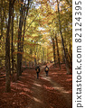 Men walk into the magical sunny forest landscape with colorful autumn season leaves. 82124395