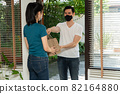 Asian man wearing a protective mask and delivering packages from grocery to young female customers at her home after online order. Concept of transportation service and express delivery and safety 82164880