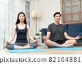 Healthy young Asian couple attractive couple practicing yoga exercises sitting on a mat in lotus pose in an online class on quarantine at home. Concept of Technology for New normal lifestyle 82164881