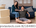 Happy young Asian couple sitting on the sofa for rest after moving to a new house on the first day. Concept of starting a new life for a newly married couple. 82164883