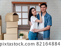 Smiling young Asian happy couple hugging boyfriend with cardboard boxes at moving day in their new home after buying real estate. Concept of starting a new life for a newly married couple. 82164884