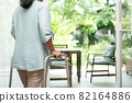 A sad old elderly woman uses Walker for standing in front of windows and looking outside and feeling lonely. Concept of depression caused by illness and Elderly caregivers 82164886