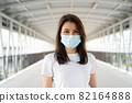 Portrait of a young woman in a medical mask for anti-coronavirus COVID-19 pandemic infectious disease outbreak protection in Public area. Concept of Virus pandemic and pollution (PM2.5) 82164888